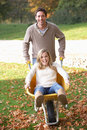 Man pushing wife through autumn leaves Royalty Free Stock Photo