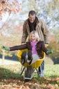 Man pushing wife in wheelbarrow Royalty Free Stock Photo