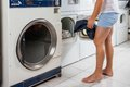 Man putting clothes in washing machine low section of young at laundromat Royalty Free Stock Images