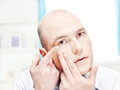Man putting contact lens in his eye Royalty Free Stock Photos