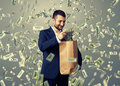 Man putting dollar s in the paper bag smiley glad businessman standing under money rain and Royalty Free Stock Images