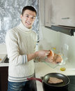 Man putting raw steak of fish into frying pan handsome at kitchen Royalty Free Stock Photos