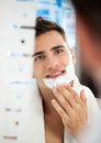 Man putting shaving cream young on his face Stock Images