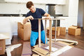 Man putting together self assembly furniture in new home by himself concentrating Stock Photography