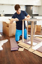 Man putting together self assembly furniture in new home kneeling on floor using screwdriver Stock Images