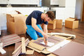 Man putting together self assembly furniture in new home using screwdriver Stock Photos