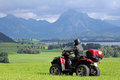 A man on quad before the mountains in Bavaria Royalty Free Stock Image