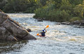 Man rafting with kayak on a fast watercourse rear view of passing through cliffs and forested areas Stock Photo