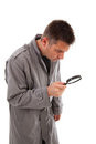 Man with raincoat is looking with magnifying glass Royalty Free Stock Image