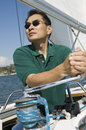 Man raising sail on sailboat asian the against clear sky Royalty Free Stock Photography