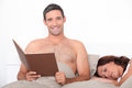 Man reading in bed as his partner sleeps Stock Photo