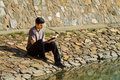 Man reading bible by lake young sitting a the Royalty Free Stock Photo