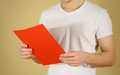Man reading blank red A4 paper. Read detailed booklet. Leaflet p Royalty Free Stock Photo