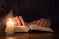 Man reading book with candle light Royalty Free Stock Photo