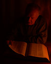 A man reading a book by candlelight an old in the night Royalty Free Stock Images