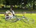 Man reading a book laying down on grass reads the next to his bicycle in clissold park london Royalty Free Stock Image