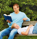 Man reading book while woman relaxing on his lap Stock Photos