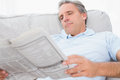 Man reading the news on couch at home in living room Stock Photos