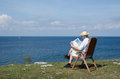 Man reading newspaper in a chair at a beautiful view Royalty Free Stock Photo
