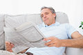 Man reading the newspaper on couch at home in living room Stock Photos
