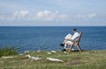 Man reading newspaper at seaside with beautiful view Royalty Free Stock Photo
