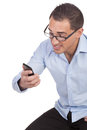Man reading a text message on his mobile wearing glasses sitting looking at it with excited anticipation isolated white Royalty Free Stock Photos