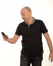 Man receiving good news in dark clothes holding mobile at arms length smiling as he receives white background Royalty Free Stock Image