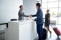 Man at reception hall and receptionist handshake Royalty Free Stock Image