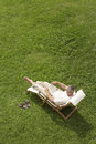 Man reclining on lawn in deck chair reading book high angle view of middle aged garden Royalty Free Stock Photos