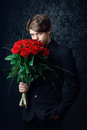 Man with a red roses young handsome dressed in black suit bouquet of Stock Photos