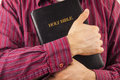 Man red shirt hugging holy bible Royalty Free Stock Images