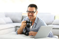 Man with reflex camera and laptop at home Royalty Free Stock Photo