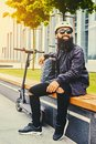 A man relaxing on a bench after riding by electric scooter. Royalty Free Stock Photo