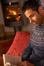 Man Relaxing With Book By Cosy Log Fire Stock Photo