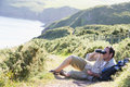Man relaxing on cliffside path using binoculars Stock Images