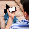 A man relaxing on a couch looking at a smartphone Stock Photography