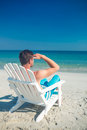 Man relaxing on deck chair at the beach a sunny day Stock Photography
