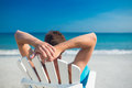 Man relaxing on deck chair at the beach a sunny day Royalty Free Stock Images