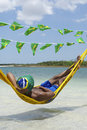 Man relaxing in hammock on brazilian beach over the sea with flag bunting Stock Photos