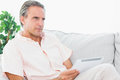 Man relaxing on his couch using tablet pc at home in living room Royalty Free Stock Photography