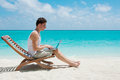 Man relaxing with laptop on the beach at maldives island ocean view Stock Images