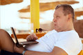 Man relaxing with a laptop at beach resort reclining on comfortable chair under straw umbrella staring thoughtfully Royalty Free Stock Photos