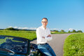 Man relaxing leaning on a cabriolet car successful handsome parked in rural road running through green field under sunny Royalty Free Stock Photo