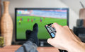 Man is relaxing with legs on table and is watching football match on TV Royalty Free Stock Photo