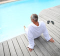 Man relaxing near swimming pool senior with spa bathrobe by Stock Photos