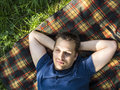 Man relaxing on a picnic blanket in green grass Royalty Free Stock Photography