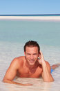 Man relaxing in sea on beach tropical beach smiling Stock Photos