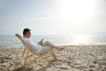 Man relaxing with tablet on the beach sitting on a deckchair Royalty Free Stock Photo