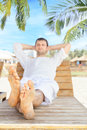 Man relaxing in tropical resort lying down on beach chair and Royalty Free Stock Photos