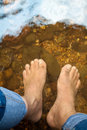Man relaxing is wet bare foot in stream in the holiday Stock Photography